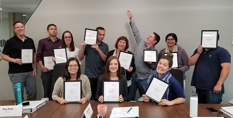 A group of Binnie management training graduates holding their certificates