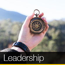 An image of a person holding a compass that links to our leadership page